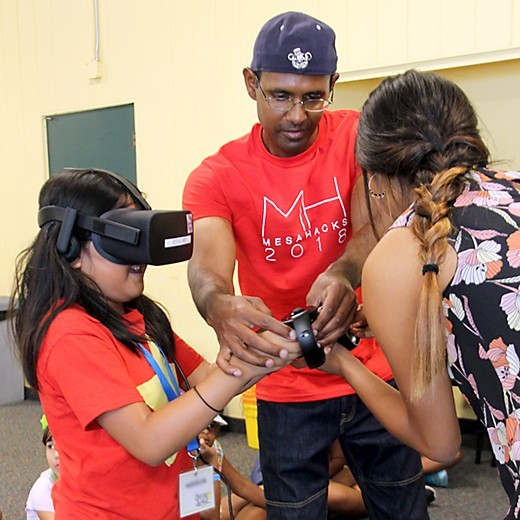 Two volunteers help a girl set up a virtual reality experience